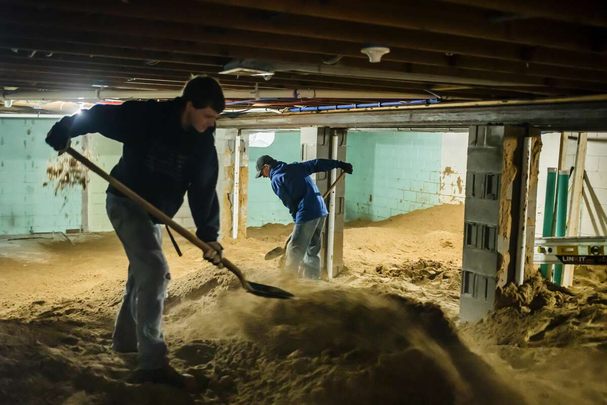Dakota Moe, left, and Tyler Page, right, both employees of OTLC Construction, spread out sand as it moves down a conveyor belt on a truck from Gushow & Sons Inc. into the basement of Steve and Joyce Saxton Friday morning, Nov. 13, 2020 on St. Mary's Drive in Midland. (Katy Kildee/kkildee@mdn.net)