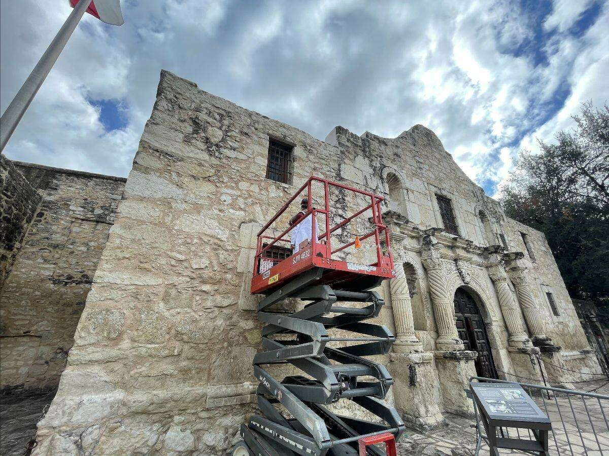 Pamela Jary Rosser, the Alamo's longtime on-site conservator, stands on an electric lift as she extracts pigments from the facade of the mission-era church. Pigment samples collected over the next four to six weeks will be studied to determine whether the church might have been painted in the 1700s, as was the custom in the indigenous mission communities.