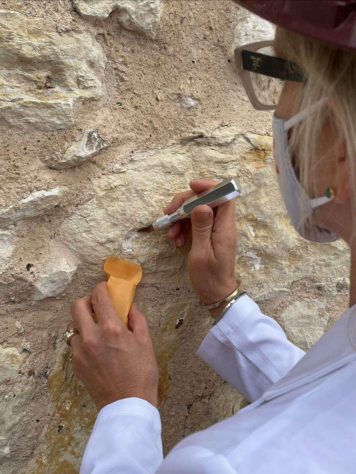 Pamela Jary Rosser, the Alamo's longtime on-site conservator, carefully removes fragments of pigment from the facade of the mission-era church. The samples will be tested to identify their age and help determine whether the church might have been painted in the 1700s, as was the custom in indigenous mission communities.