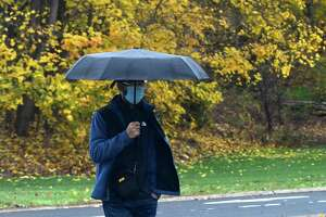 A pedestrian uses an umbrella to stay dry from a light rain on Friday, Nov. 13, 2020 in Albany, N.Y. (Lori Van Buren/Times Union)