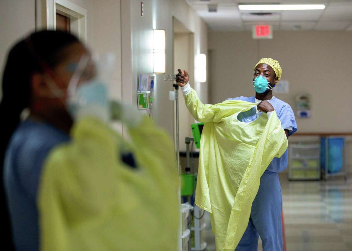Registered nurses Constantine Mziwanda, right, and Brenda Debose, left, get into PPE before checking on their COVID-19 patients at Houston Methodist West-Continuing Care Hospital on Friday, Nov. 13, 2020, in Houston.