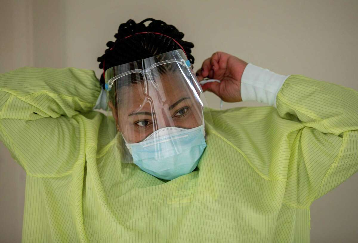 Brenda Debose, a registered nurse, adjusts her PPE before entering a Highly Infectious Disease Unit room where a patient with COVID-19 is being treated at Houston Methodist West-Continuing Care Hospital on Friday, Nov. 13, 2020, in Houston.