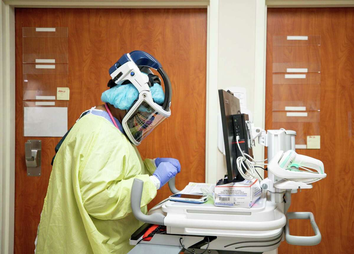 Respiratory therapist Kenny O., who did not want to give her last name, checks on COVID-19 patients at the Highly Infectious Disease Unit of Houston Methodist West-Continuing Care Hospital, on Friday, Nov. 13, 2020, in Houston.