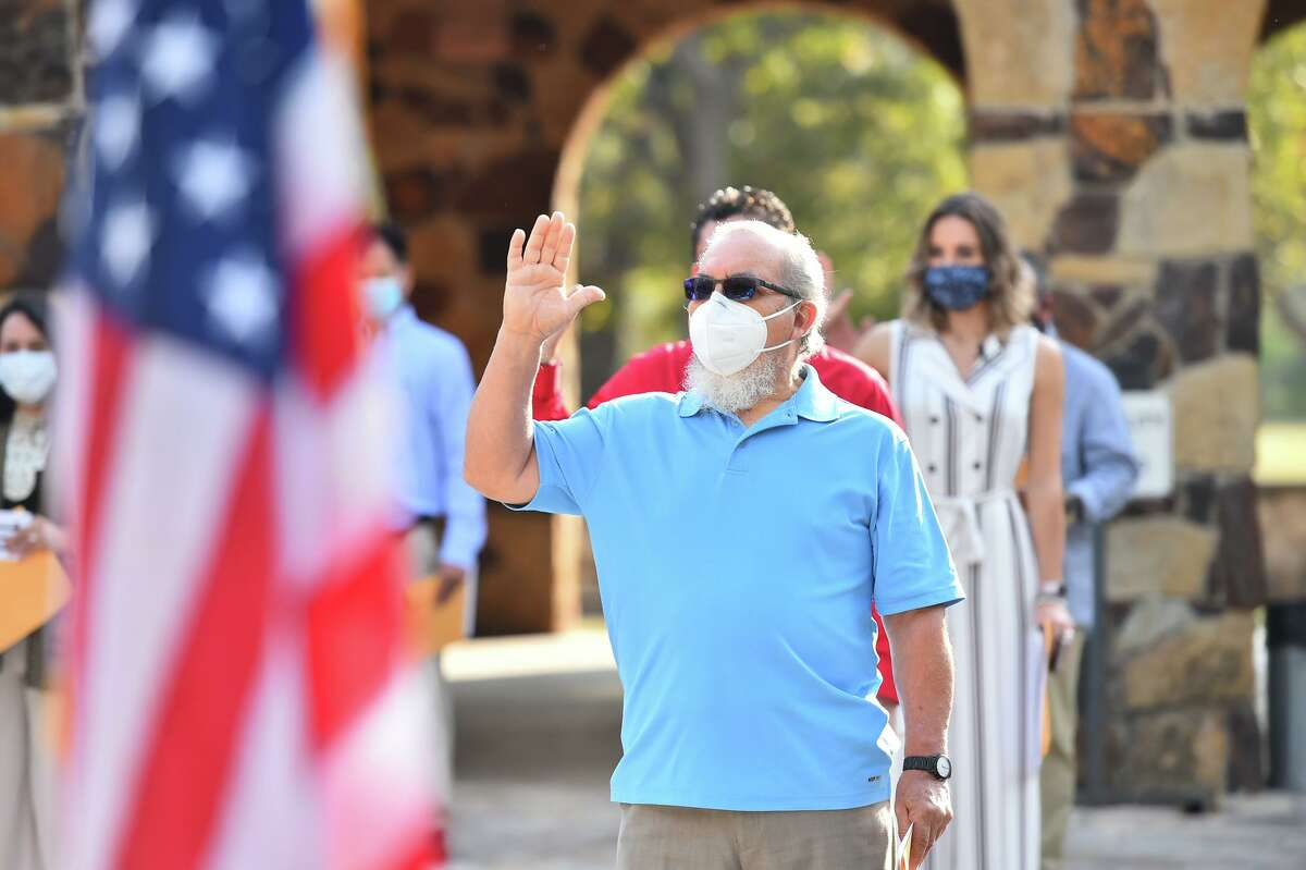 Jesus Juarez takes the oath of citizenship during a naturalization ceremony Friday morning at the Joske Pavilion in Brackenridge Park. The 240 citizenship candidates originate from 60 countries as diverse as Australia, Brazil, Cameroon, Cuba, Egypt, Italy, Mexico, Romania and Zambia.