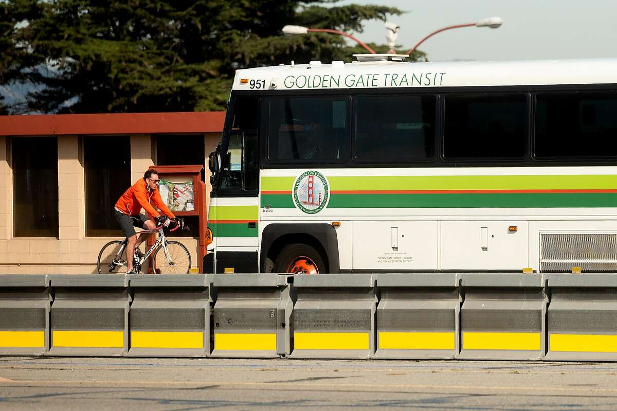 A bicyclist passes a Golden Gate Transit bus on Tuesday, Nov. 10, 2020, in San Francisco.