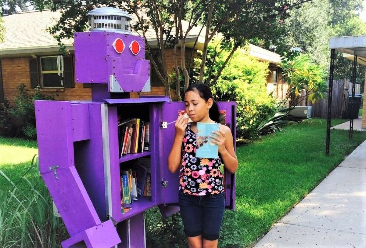 Madeline Baggett stands next to her family's Little Free Library in Oak Forest.