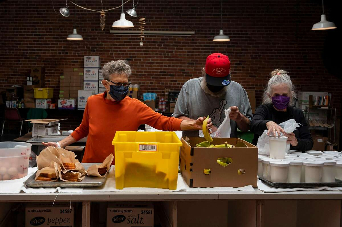 Martin de Porres House of Hospitality Director Mim Locke, Jeff Leggett and Patti Toomey assemble bagged meals for guests in S.F. Traditionally, 200 volunteers prepare the Thanksgiving dinner; this year, it's eight.