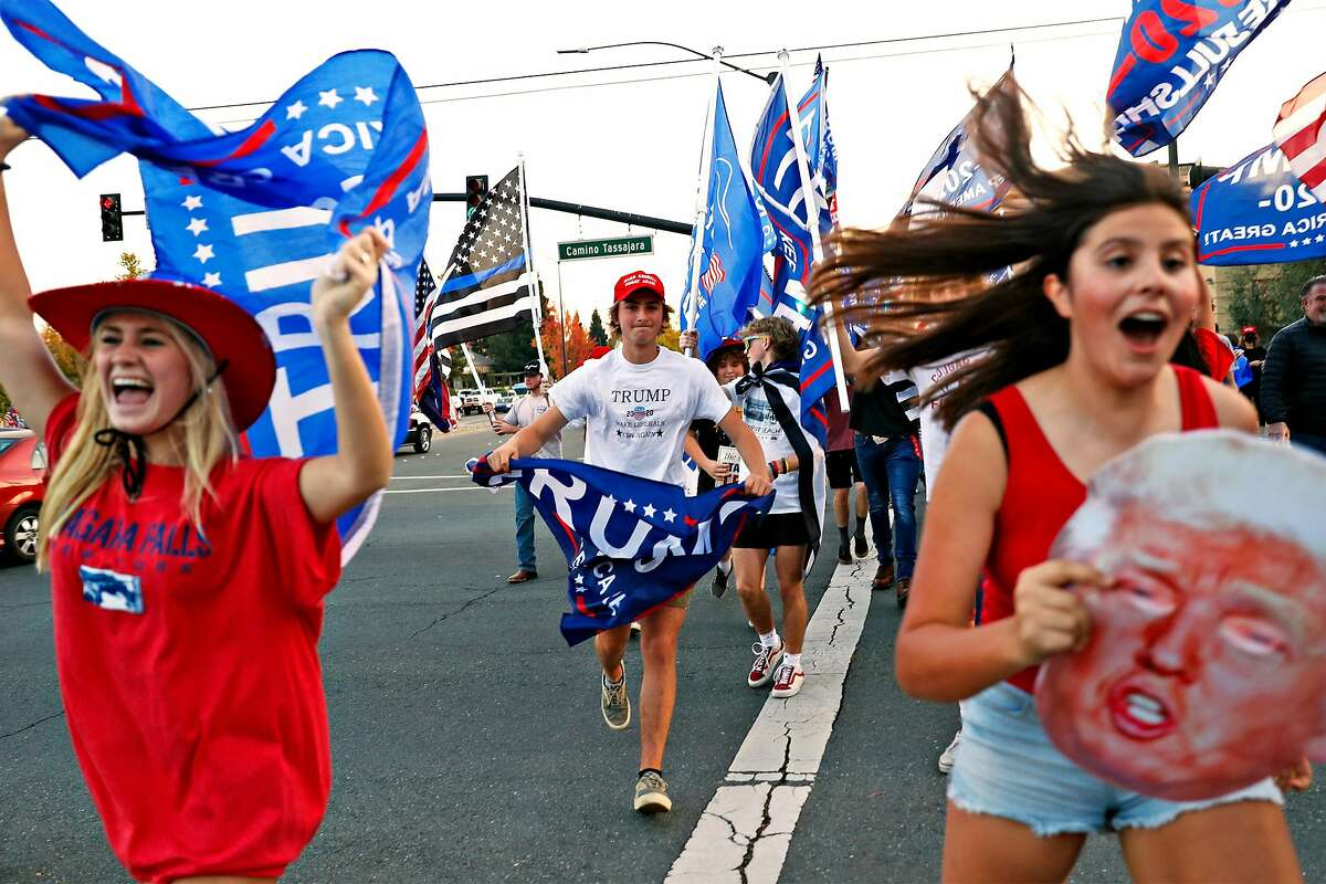 Supporters of President Trump run across Crow Canyon Road during a rally in Danville on the day before election day. The prospect of a unified America seems out of reach even after Joe Biden has been declared winner of the presidency.