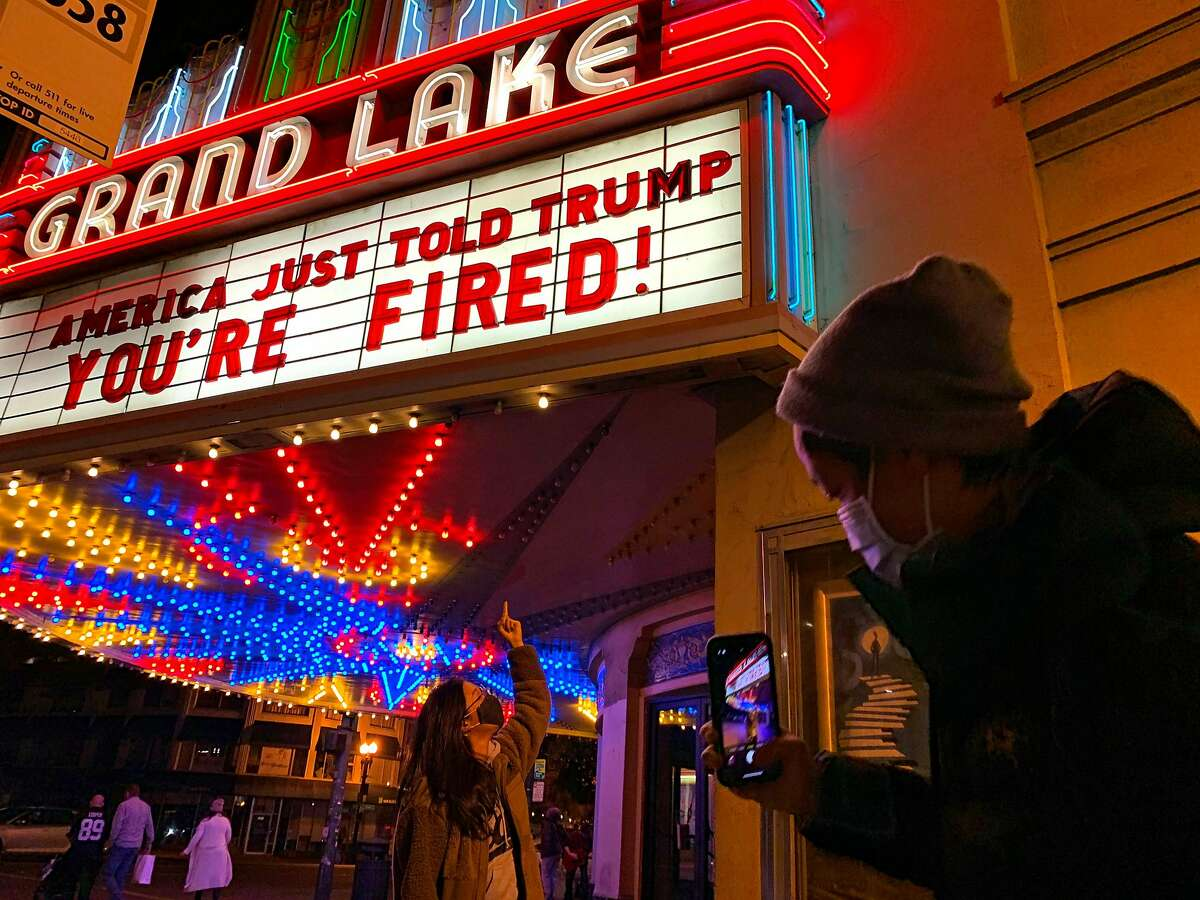 Adrienne Lam has her photo taken by Andrew Lee under the marquee at Oakland's Grand Lake Theatre that hails Biden's victory.