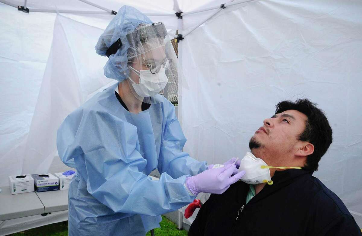 Nurse Practitioner Julianna Barresi, APRN administers a Rapid Oral Covid-19 test to Greenwich resident Walter Aucay, 36, at a testing site set up at the Family Center at Wilbur Peck Court in Greenwich, Connecticut on May 1, 2020. Some 60 Rapid Covid-19 test were performed, yielding results in less than a day.