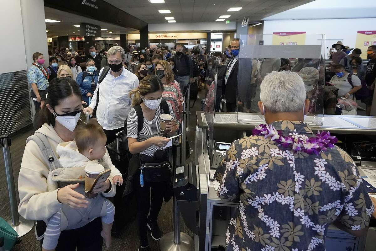 United Airlines passengers walk past the gate to board a flight to Hawaii on Oct. 15, 2020, at San Francisco International Airport in San Francisco.