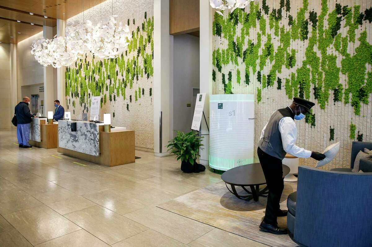 Zakayo Neriko, right, organizes the lobby while an IVP Air filtration unit filters air Monday, Sept. 28 2020, at the InterContinental Houston-Medical Center hotel in Houston.