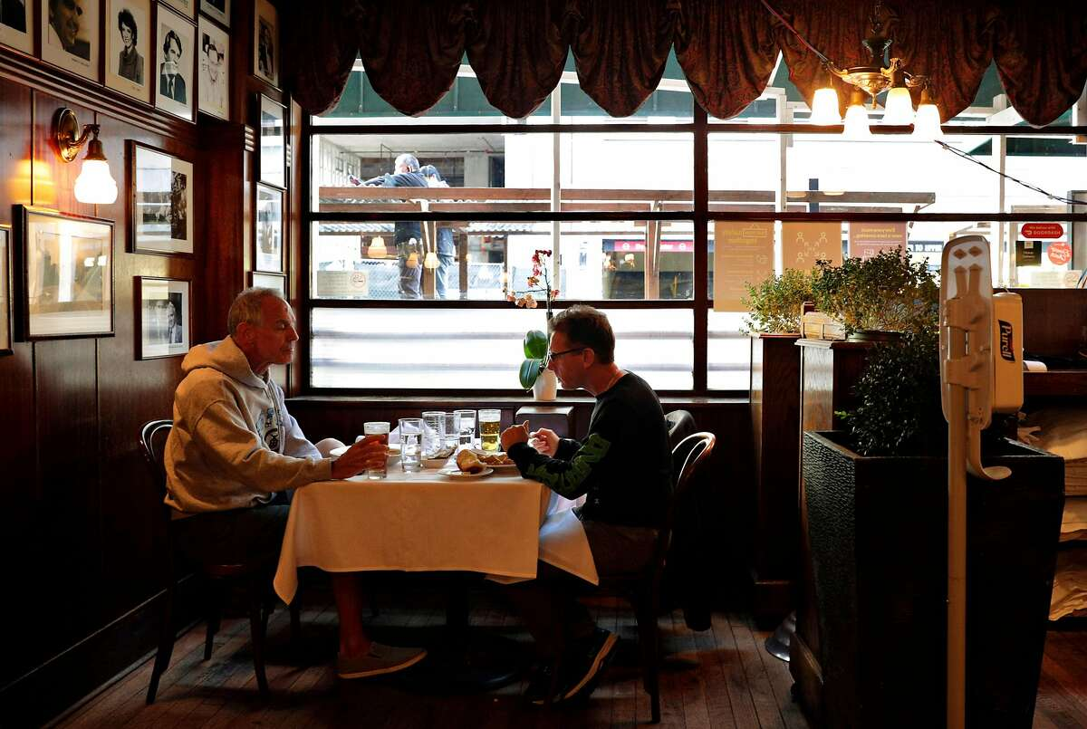 Joe Dwyer (left) and Hugh Lytle have lunch at John's Grill as a dining area is constructed outside in San Francisco on Tuesday. Citing a concerning surge in cases and a rise in the average testing positivity rate in the city to 1.28%, Mayor London Breed announced a set of new restrictions during a briefing Tuesday. At the end of the day Friday, the city will once again restrict indoor dining, pause reopening high schools, and instill new capacity limits for gyms and movie theaters.