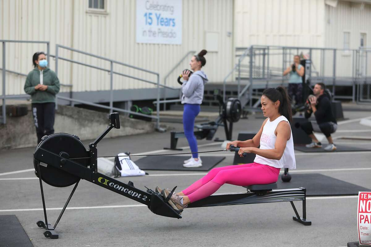 Lisa Khouri (front) of San Francisco uses a rowing machine during a San Francisco CrossFit class with coach Yasmen Mehta. The famous gym will close Sunday.