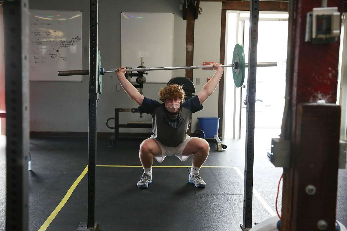 Mason Tuller lifts weights as he works out at at San Francisco CrossFit. San Francisco is moving to restrict gyms' indoor capacity again.