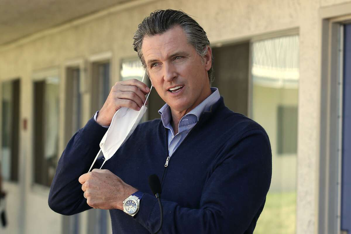 Gov. Gavin Newsom removes his face mask before giving an update during a visit to Pittsburg, Calif. on June 30, 2020.