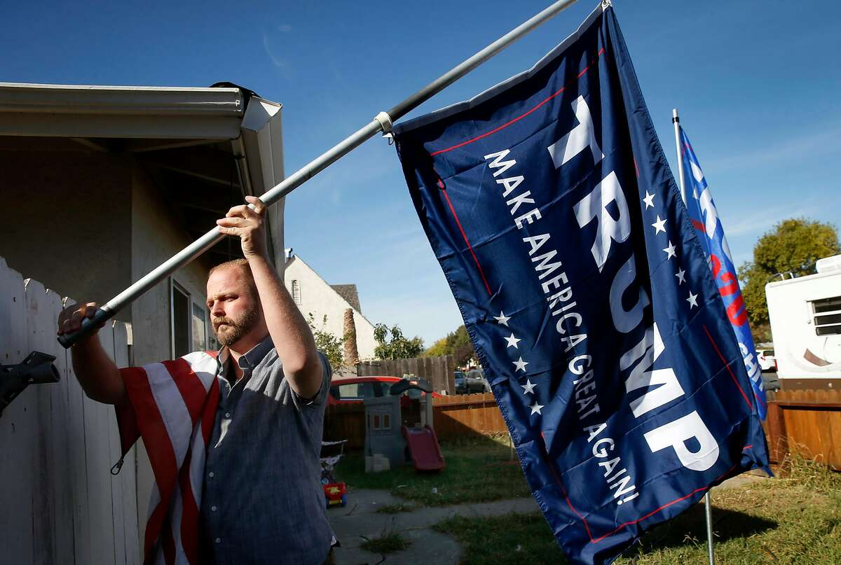 Justin Y., who didn't want to use his last name to protect his family, relocates a Trump flag that was flying in his front yard in Fairfield after the election. He believes the claims of voter fraud.
