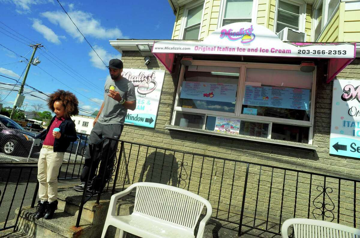 Customers Sydney Woods, 6, and her dad Daryl enjoy some Italian Ice at Micalizzi's Italian Ice in Bridgeport, Conn., on Thursday Apr. 27, 2017. Micalizzi's is celebrating its 40th anniversary.