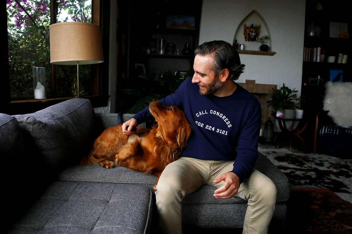 Joseph Killian, 38, pets his dog, Bishop, in their home on Friday, November 13, 2020, in San Francisco, Calif. Killian and friends donated $50,000 to half dozen Democratic Senate candidates -- and most of them lost. Now, with the Senate -- and Joe Biden's ambitious agenda -- on the line, he wants to move to Georgia to knock on doors and volunteer for the two Democrats in a special election there. But, he like many other Californians itching to get involved in Georgia, are hesitating. Is it a bad look for a ton of outside money to roll into Georgia from liberal California -- much less showing up to knock on doors? Californians are trying to best figure out how to get involved in a Senate race across the country without screwing it up.