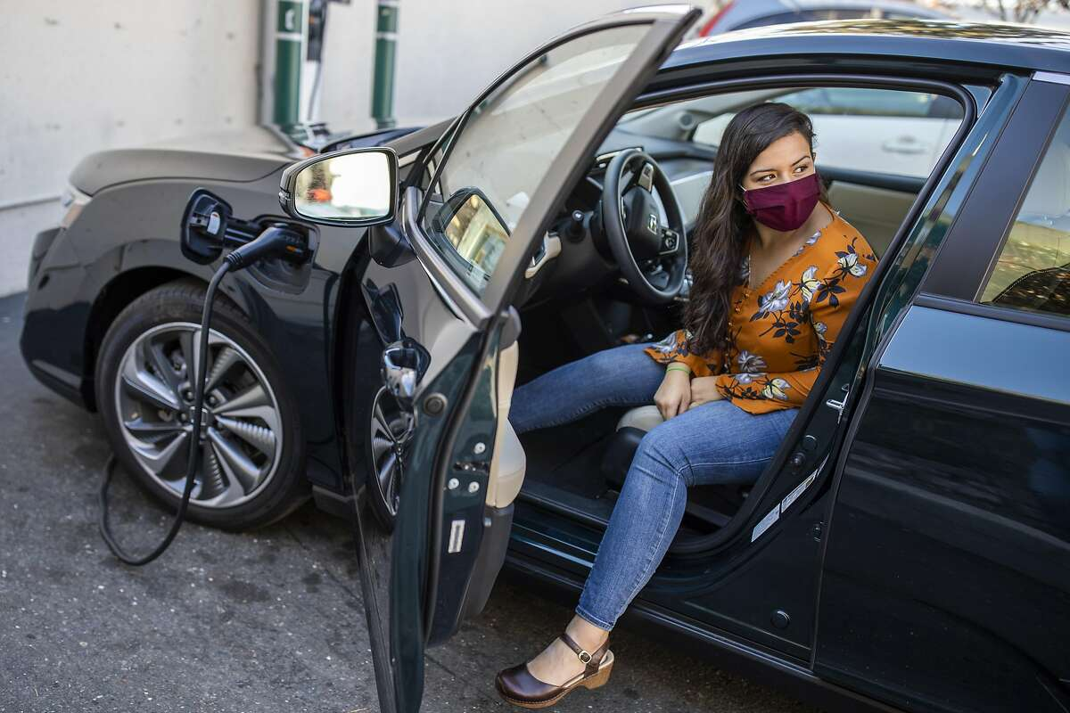 Maya Katz-Ali waits as her new car, her first plug-in hybrid, charges at a station on Lakeshore Avenue in Oakland.
