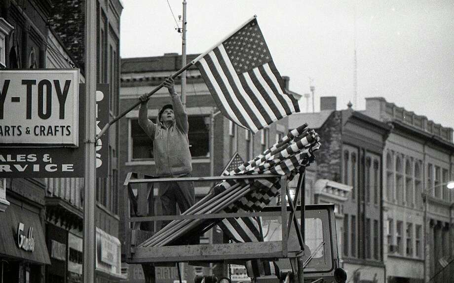 City of Manistee employee Harry Gorch hangs flags along River Street in observance of Veterans Day. The photo was originally published on the front page of the News Advocate in the Nov. 10, 1980 issue. (Manistee County Historical Museum photo)