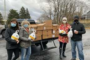 (From left) Jenna Vincent, Em Vincent, Meagan Kempf, Chris Kempf, of Re/Max Bayshore Properties contributed $1,300 in funding toward the purchase of turkeys that were then distributed at a Matthew 25:35 food pantry drive thru on Friday.