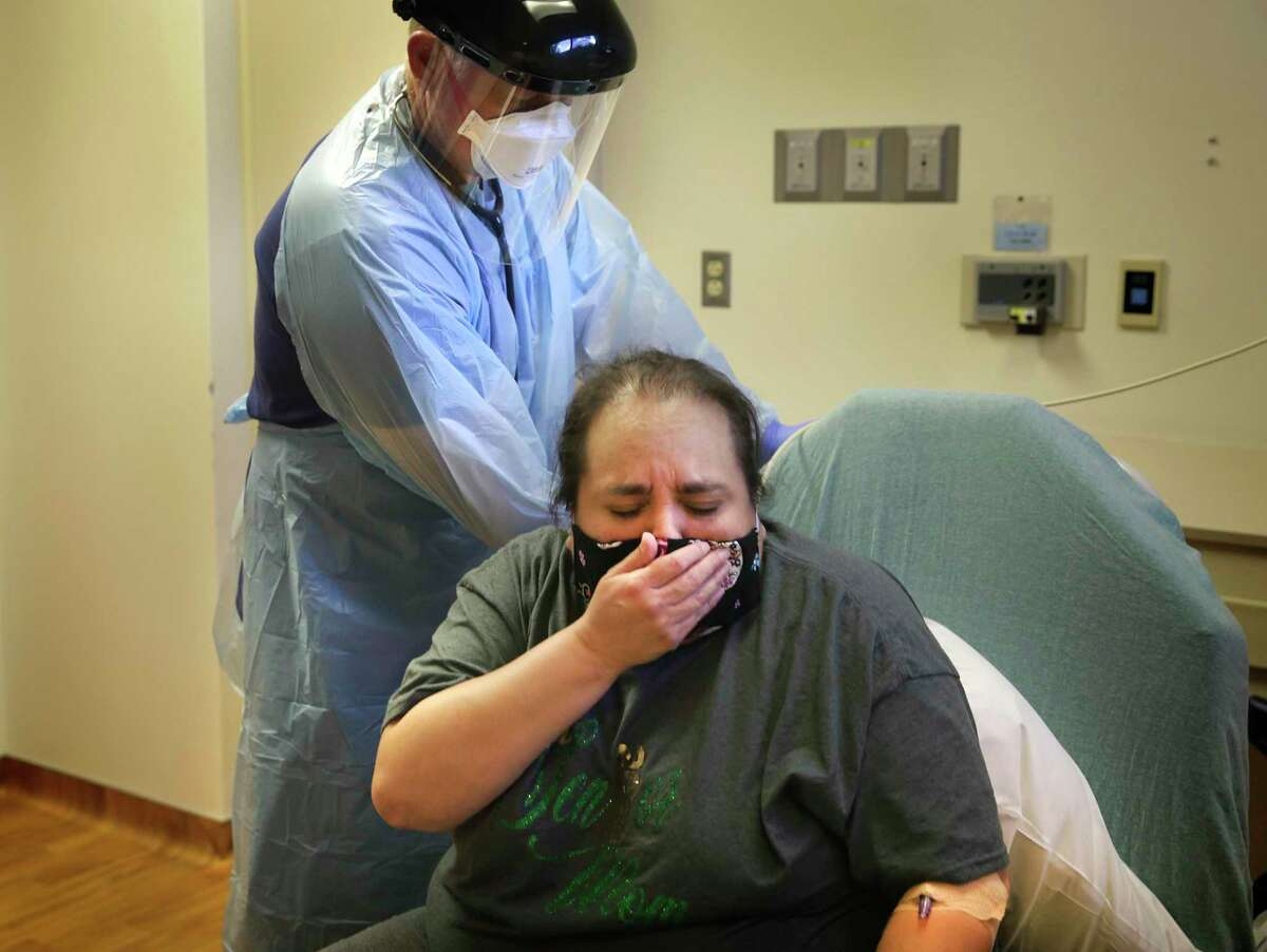 Melissa Paez-Villarreal, who tested positive for the coronavirus, covered a cough as Dr. Corey Harrison checked her vitals in Christus Santa Rosa Hospital's emergency room in the medical center in July. Harrison is the medical director of the hospital's emergency room.