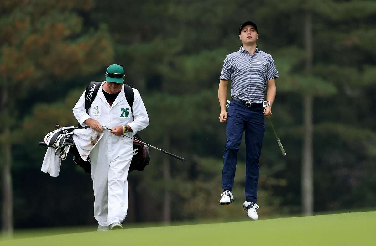Justin Thomas (right) leaps for a better view of his lie on the 14th hole during Friday's play at Augusta National. Thomas has a share of the Masters lead.