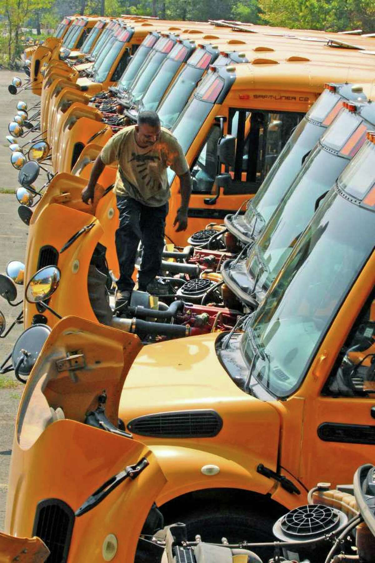 Durham Bus Company mechanic Ram Rambharose inspects belts and hoses during a safety inspection of the bus fleet on Wednesday that will service the Troy School District in Watervliet. ( Michael P. Farrell / Times Union )
