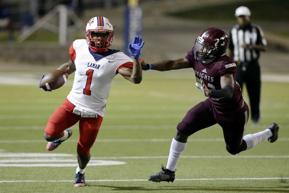 Lamar Texans receiver Roshane Cruickshank (1) is caught by Heights Bulldogs' Dylan Harris (23) during the first half of a high school football game at Delmar Stadium Friday, Nov. 13, 2020 in Houston, TX.