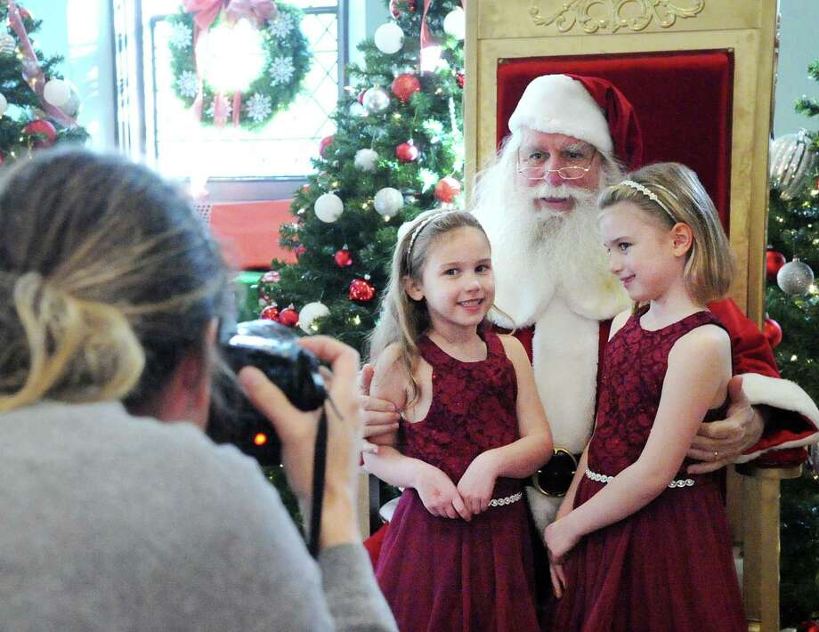 Greenwich residents Stella Smith, 6, left, and her sister, Lily Smith 7, wore matching maroon dresses as they had their photo taken with Santa during the Junior League of Greenwich annual Enchanted Forest event at Christ Church in 2017. The Enchanted Forest will be moving online due to the pandemic. People can begin reserving special events for their families now. Photo: File / Bob Luckey Jr. / Hearst Connecticut Media / Greenwich Time