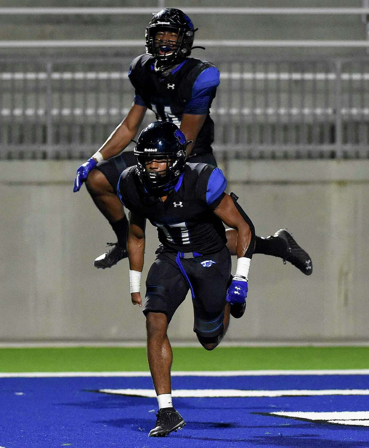 CE King defensive back Ja'Kobe Crawford (17) and linebacker Will Hicks celebrate stopping Atascocita on fourth down during the second half of a high school football game, Friday, Nov. 13, 2020, in Houston.