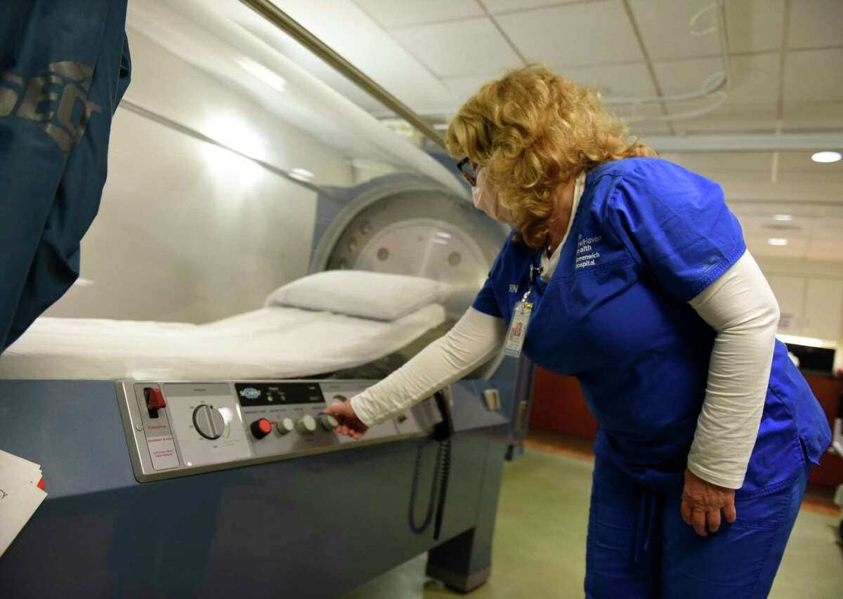 Ellen Stacom, RN, demonstrates the hyperbaric oxygen chamber at Greenwich Hospital in Greenwich, Conn. Thursday, Nov. 5, 2020. Greenwich Hospital will be taking part in a year-long trial that will examine treatment for COVID-19 through the use of hyperbaric oxygen therapy.