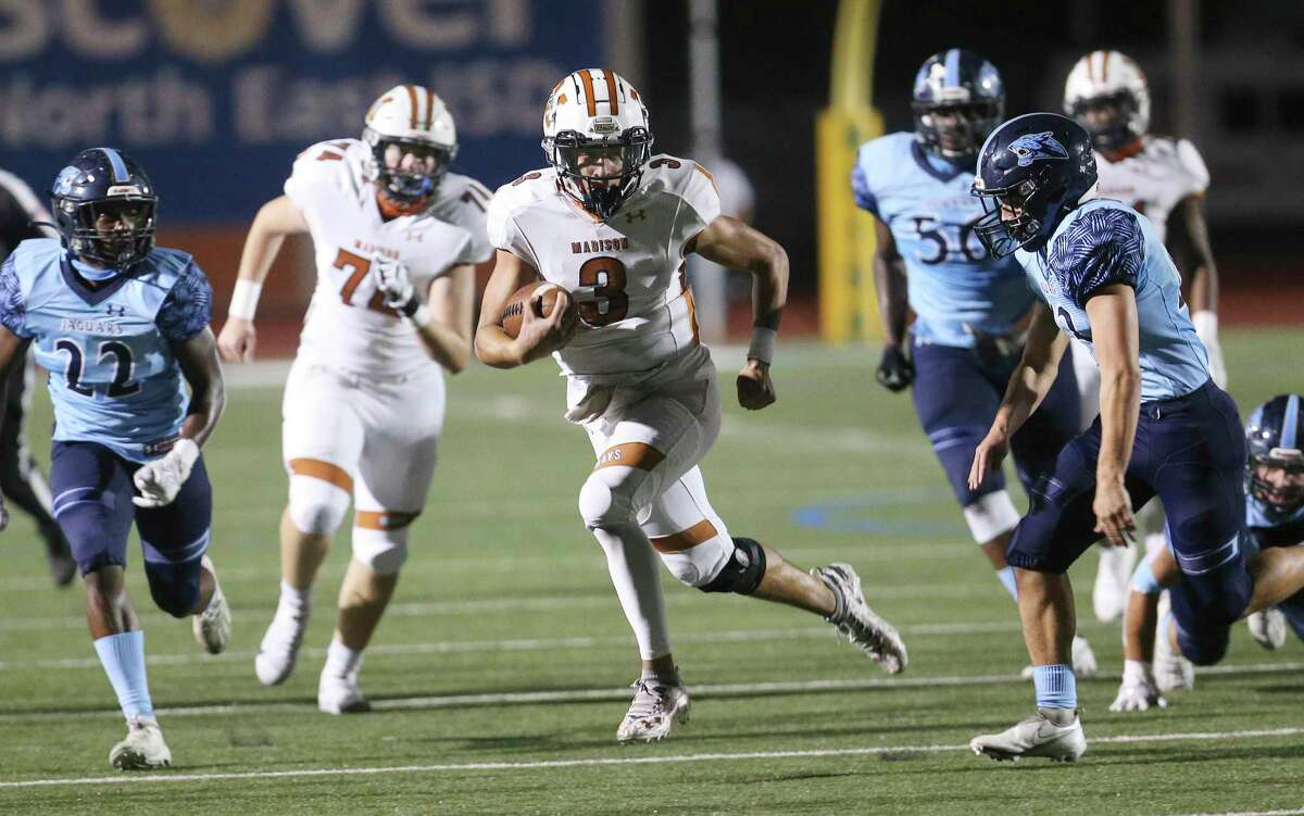 Madison quarterback Royal Kyle (03) sprints for yardage against Johnson's Justin Kirk (43) and Madison Thomas (22) during their football game at Heroes Stadium on Friday, Nov. 13, 2020.