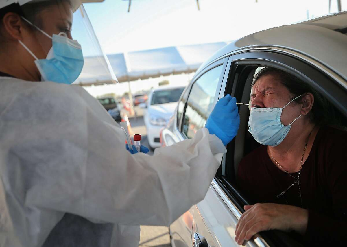 A woman receives a nasal swab test at a drive-in COVID-19 testing site amid a surge of COVID-19 cases on November 13, 2020 in El Paso, Texas.