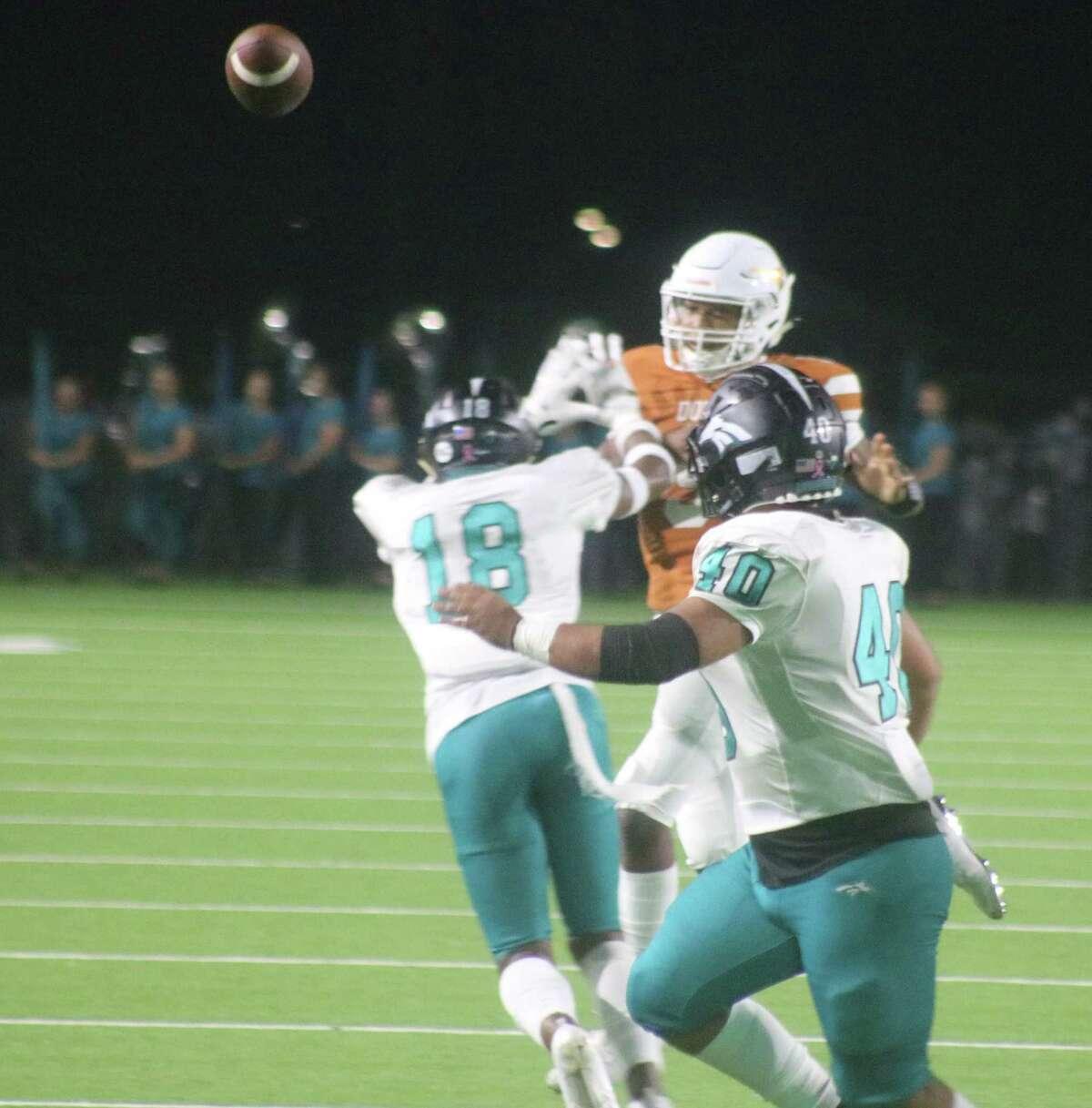 Dobie quarterback Cameron Gray throws a pass against the Memorial rush in second-quarter action Friday night.