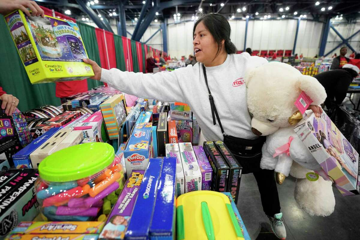Leticia Ibanez picks up toys for her nine children, who range in age from 2 to 19-years-old, during the Houston Children's Charity Annual Christmas Toy Distribution at George R. Brown Convention Center Friday, Dec. 20, 2019, in Houston. The Houston Children's Charity partnering with the U.S. Marines' Toys for Tots program and the Houston First Corporation will give an estimated 80,000 toys to the parents of over 20,000 children in need.