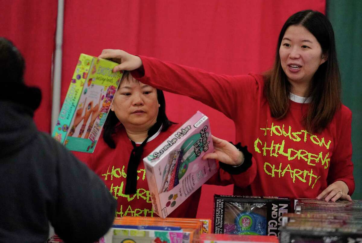 Volunteers Christy Li, left, and Chang Bu, right, hand out toys during the Houston Children's Charity Annual Christmas Toy Distribution at George R. Brown Convention Center Friday, Dec. 20, 2019, in Houston. The Houston Children's Charity partnering with the U.S. Marines' Toys for Tots program and the Houston First Corporation will give an estimated 80,000 toys to the parents of over 20,000 children in need.