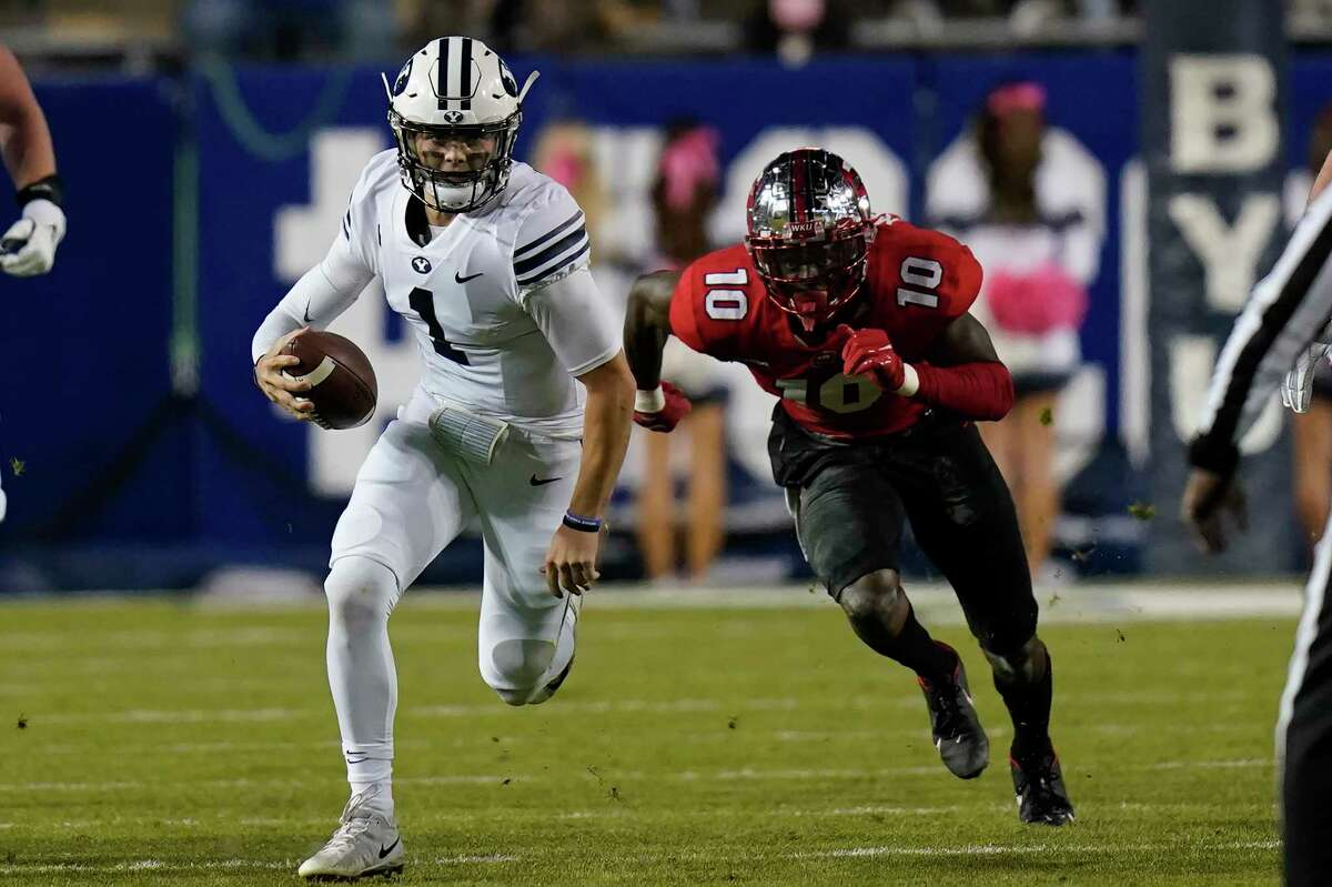 FILE - BYU quarterback Zach Wilson (1) out runs Western Kentucky defensive end DeAngelo Malone (10) during the first half of an NCAA college football game Saturday, Oct. 31, 2020, in Provo, Utah.