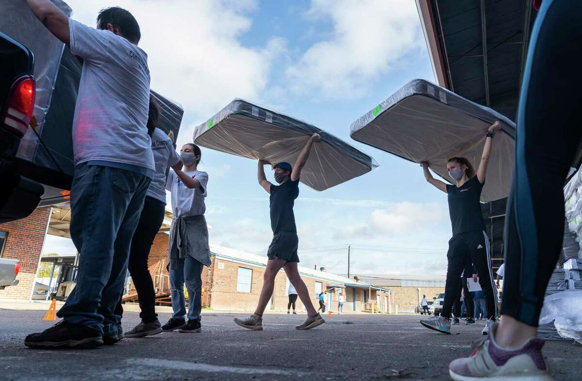 Volunteers load mattresses into a waiting vehicle, Saturday, Nov. 14, 2020, at Texas Mattress Makers in Houston. 250 mattresses donated by Texas Mattress Makers were distributed along with bed frames, pillows and sheet sets from Houston Children's Charity's