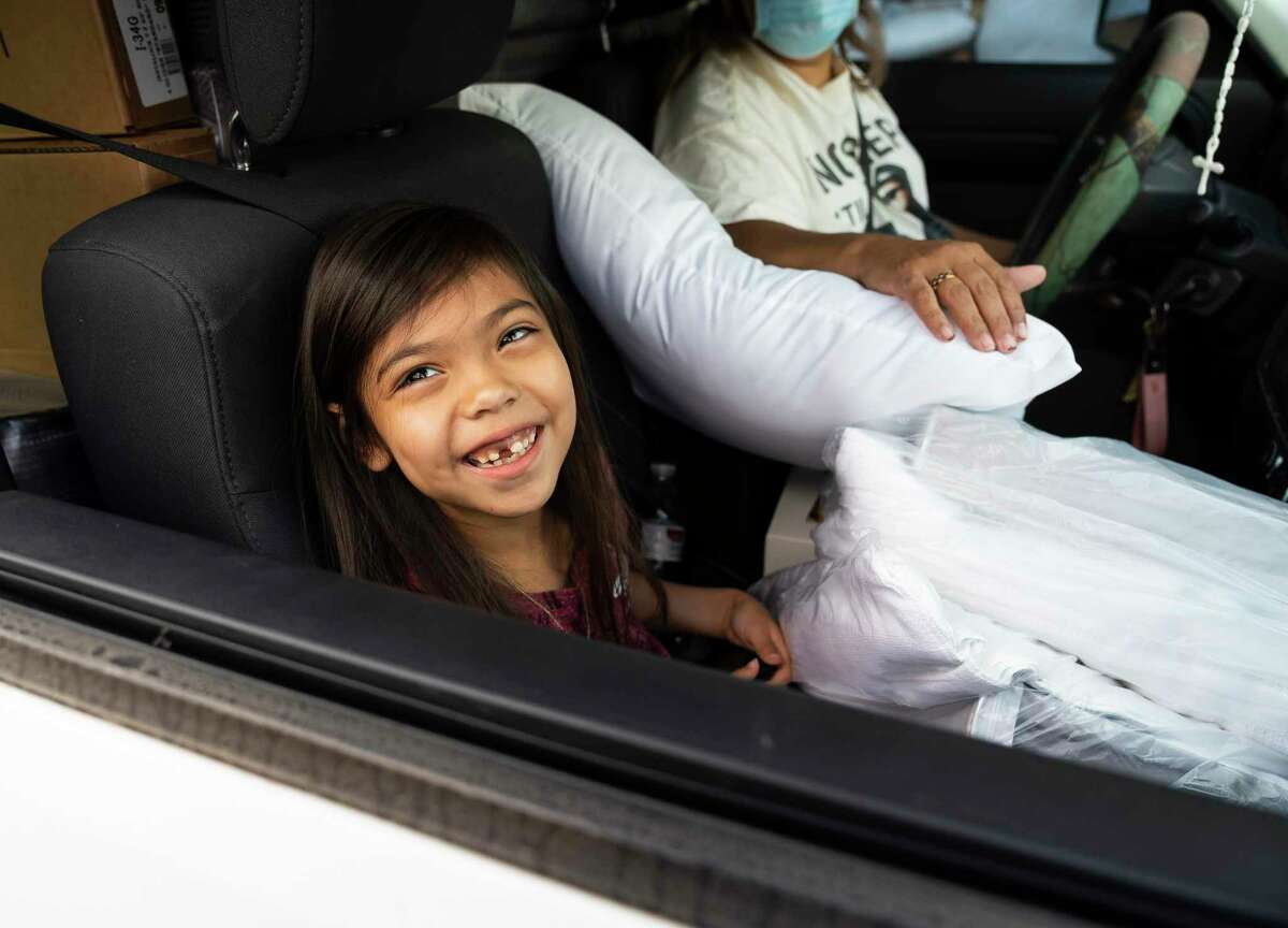 Melany Leyva, 6, smiles surrounded by the new pillows she received along with two new mattresses with her grandmother, Myra Bedolla, Saturday, Nov. 14, 2020, at Texas Mattress Makers in Houston. 250 mattresses donated by Texas Mattress Makers were distributed along with bed frames, pillows and sheet sets from Houston Children's Charity's