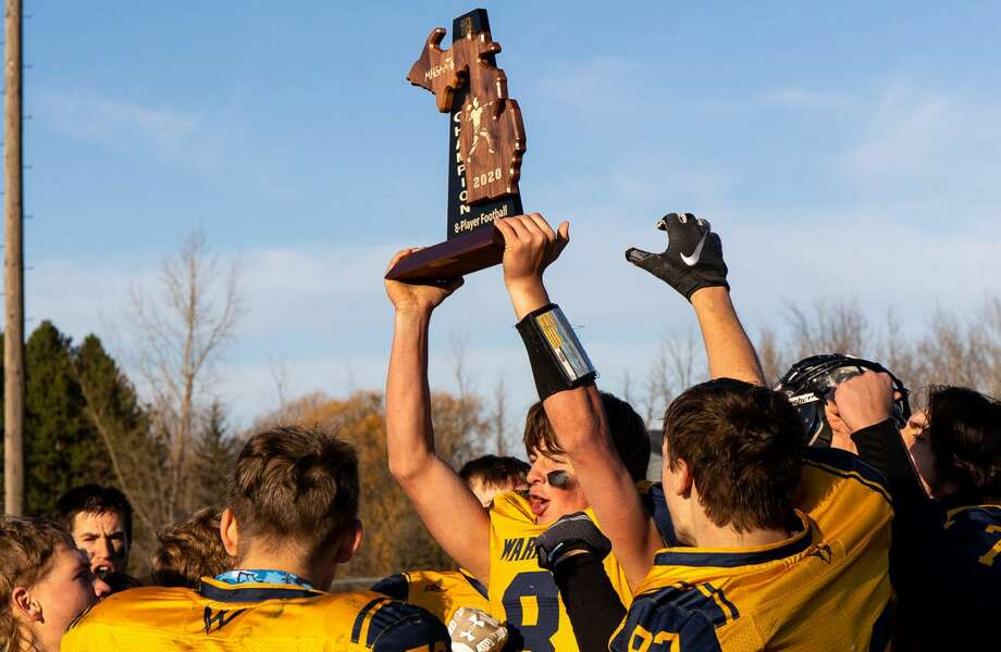 The North Huron varsity football team poses with its 2020 regional championship trophy on Saturday afternoon after defeating Mount Pleasant Sacred Heart, 50-20. / Quad N Productions