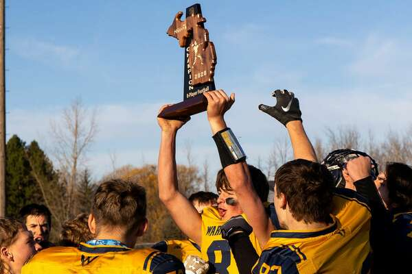 The North Huron varsity football team poses with its 2020 regional championship trophy on Saturday afternoon after defeating Mount Pleasant Sacred Heart, 50-20.