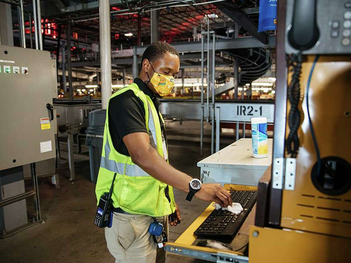 A UPS employees handles packages at one of the company's packaging centers. Company officials announced in September that they would hire more than 100,000 seasonal employees to support the anticipated increase in holiday package volume.