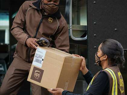 A UPS driver and a driver's helper unload a package.