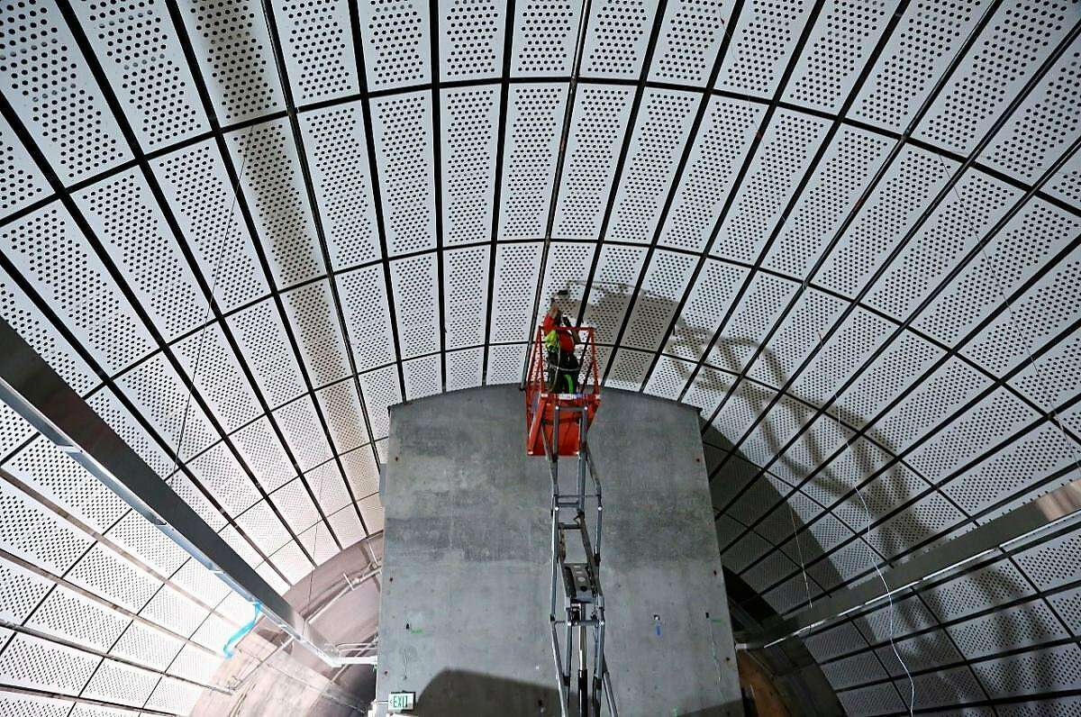 Workers install decorative panels in the Chinatown/Rose Pak Central Subway station.
