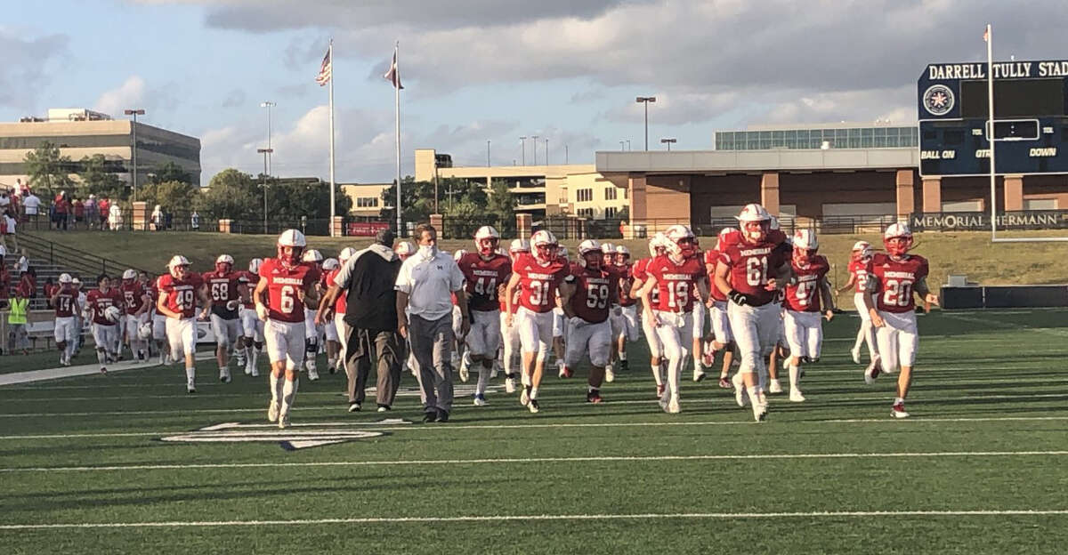 The Memorial Mustangs run off the field at Darrell Tully Stadium following their 17-7 win over the Cy Creek Cougars on Nov. 14.
