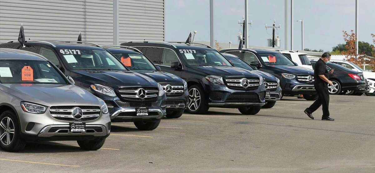 A salesman walks by a row of vehicles at Mercedes-Benz of San Antonio on Friday, Nov. 13, 2020. Managers at luxury dealerships in San Antonio such as Lexus and Mercedes said they've seen sales near or above pre-pandemic levels, while used car dealers and cheaper car models have struggled through the year. Lower-income workers appear to still be struggling, while upper-income professionals have emerged relatively unscathed from the pandemic.