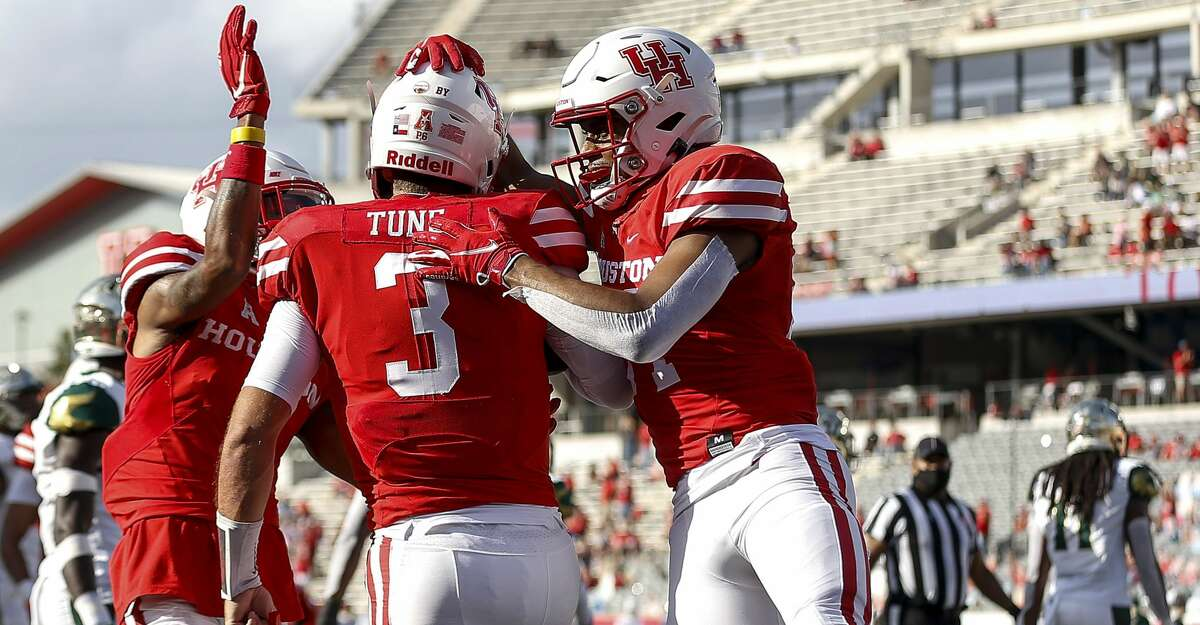 Houston Cougars wide receiver Nathaniel Dell (4) and running back Mulbah Car (34) congratulate quarterback Clayton Tune (3) after he scored a touchdown during the first quarter of an NCAA football game Saturday, Nov. 14, 2020, at TDECU Stadium in Houston.
