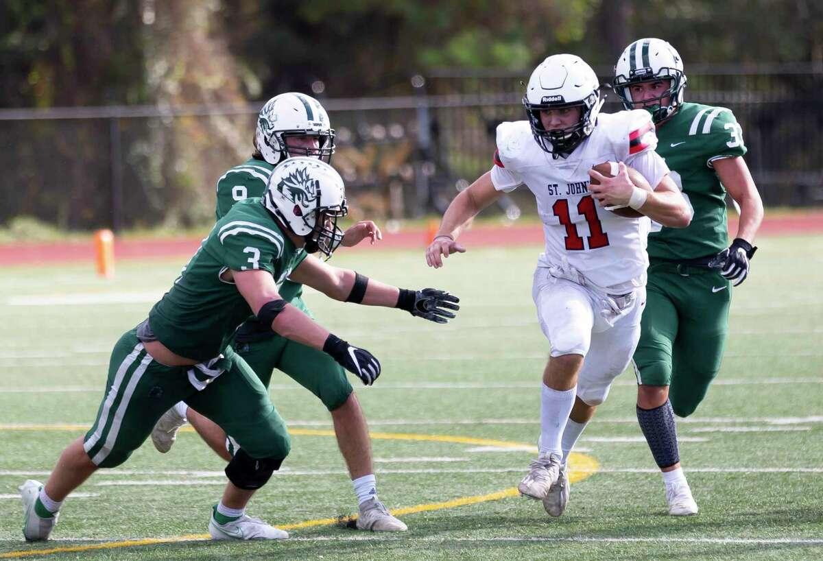 St. John's quarterback John Perdue (11) slips passed John Cooper running back Jake Peterson (3) during the third quarter of a SPC football game held at The John Cooper School, Saturday, Nov. 14, 2020, in The Woodlands.